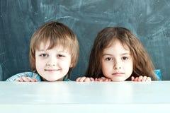 Muchacho y muchacha que ocultan detrás de una tabla Fotografía de archivo libre de regalías