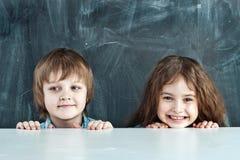 Muchacho y muchacha que ocultan detrás de una tabla Imágenes de archivo libres de regalías
