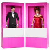 Muchacho y muchacha que parecen las muñecas en cajas Fotografía de archivo