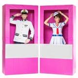 Muchacho y muchacha que parecen las muñecas en cajas Imágenes de archivo libres de regalías