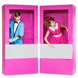 Muchacho y muchacha que parecen las muñecas en cajas Imagenes de archivo