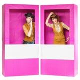 Muchacho y muchacha que parecen las muñecas en cajas Fotos de archivo