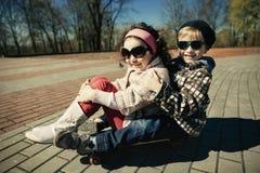 Muchacho y muchacha que patinan en la calle Imágenes de archivo libres de regalías