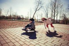 Muchacho y muchacha que patinan en la calle Foto de archivo