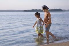 Muchacho y muchacha que recorren a lo largo del lago Imágenes de archivo libres de regalías