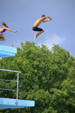 Muchacho y muchacha que saltan del trampolín Imagen de archivo