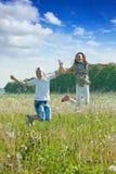 Muchacho y muchacha que saltan en el prado Imagen de archivo