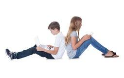 Muchacho y muchacha que se sientan de nuevo a la parte posterior Imágenes de archivo libres de regalías