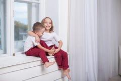 Muchacho y muchacha que se sientan en el alféizar que mira hacia fuera la ventana imágenes de archivo libres de regalías