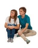 Muchacho y muchacha que se sientan en el suelo Imagenes de archivo