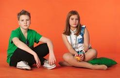 Muchacho y muchacha que se sientan en el suelo Imágenes de archivo libres de regalías