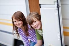 Muchacho y muchacha que se sientan en la entrada de la caravana Fotos de archivo libres de regalías
