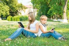 Muchacho y muchacha que se sientan en parque con la tableta digital Foto de archivo