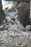 Muchacho y muchacha (10-12) que se sientan en piedras que lanzan de la roca Imagen de archivo libre de regalías