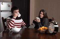 Muchacho y muchacha que se sientan en una tabla y un té de consumición Imagenes de archivo