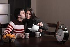 Muchacho y muchacha que se sientan en una tabla y un té de consumición Fotografía de archivo libre de regalías