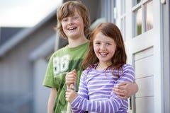 Muchacho y muchacha que se unen en la entrada de casas que acampan Imágenes de archivo libres de regalías