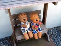 Muchacho y muchacha que sonríen y que ríen feliz mientras que se sienta en silla de madera Imagenes de archivo