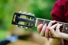Muchacho y muchacha que tocan la guitarra Imagen de archivo libre de regalías