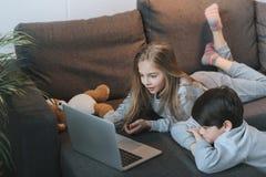 Muchacho y muchacha que usa el ordenador portátil en el sofá junto Fotos de archivo
