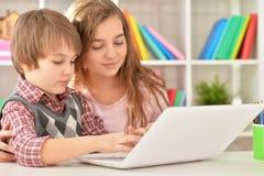 Muchacho y muchacha que usa la computadora portátil Foto de archivo libre de regalías