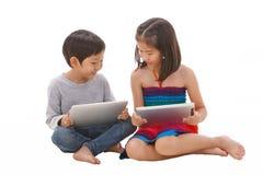Muchacho y muchacha que usa la tableta foto de archivo libre de regalías