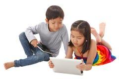 Muchacho y muchacha que usa la tableta Fotos de archivo