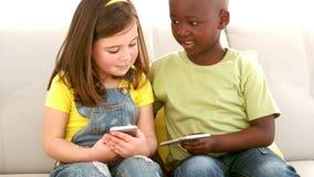 Muchacho y muchacha que usa smartphones en el sofá almacen de metraje de vídeo