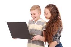 Muchacho y muchacha que usa un ordenador portátil aislado Imagen de archivo