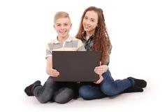 Muchacho y muchacha que usa un ordenador portátil aislado Foto de archivo