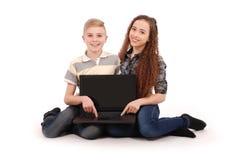 Muchacho y muchacha que usa un ordenador portátil aislado Fotografía de archivo