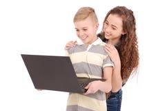 Muchacho y muchacha que usa un ordenador portátil aislado Foto de archivo libre de regalías
