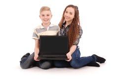 Muchacho y muchacha que usa un ordenador portátil aislado Imágenes de archivo libres de regalías