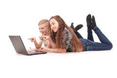 Muchacho y muchacha que usa un ordenador portátil que miente en el piso Imágenes de archivo libres de regalías