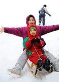 Muchacho y muchacha sledging en nieve Imágenes de archivo libres de regalías