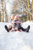 Muchacho y muchacha Sledging a través del arbolado Nevado Imagen de archivo