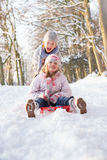 Muchacho y muchacha Sledging a través del arbolado Nevado Imágenes de archivo libres de regalías