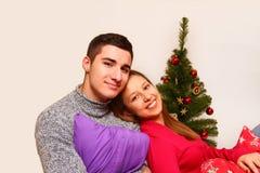 Muchacho y muchacha sonrientes con almohadas y un árbol de navidad   Imagen de archivo libre de regalías