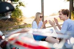 Muchacho y muchacha sonrientes en las gafas de sol que se sientan en piso y alegre que juegan con las manos El hablar hermoso jov Fotografía de archivo