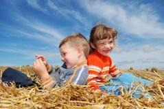 Muchacho y muchacha sonrientes en paja al aire libre Imagenes de archivo