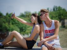 Muchacho y muchacha sonrientes felices en un fondo del parque Novio y novia que toman imágenes Concepto progresivo de la juventud Imagen de archivo
