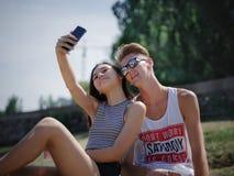 Muchacho y muchacha sonrientes felices en un fondo del parque Novio y novia que toman imágenes Concepto progresivo de la juventud Fotografía de archivo