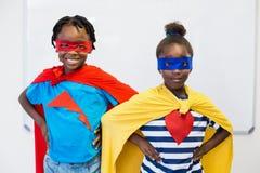 Muchacho y muchacha sonrientes que fingen ser un super héroe Foto de archivo