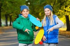 Muchacho y muchacha sonrientes que sostienen el penique del plástico del color Fotografía de archivo libre de regalías