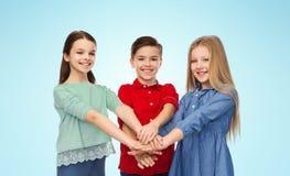 Muchacho y muchachas felices con las manos en el top Imagen de archivo libre de regalías