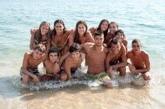 Muchacho y muchachas que se sientan en el escritorio que practica surf y la mirada en el mar azul Foto de archivo