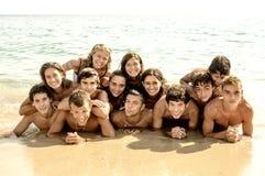Muchacho y muchachas que se sientan en el escritorio que practica surf y la mirada en el mar azul Fotografía de archivo