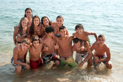 Muchacho y muchachas que se sientan en el escritorio que practica surf y la mirada en el mar azul Imagenes de archivo
