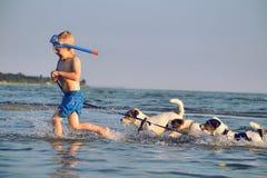 Muchacho y muchachas que se sientan en el escritorio que practica surf y la mirada en el mar azul Fotos de archivo