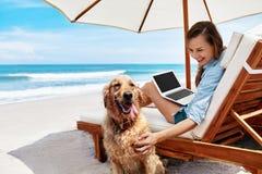 Muchacho y muchachas que se sientan en el escritorio que practica surf y la mirada en el mar azul Mujer que usa el ordenador port foto de archivo libre de regalías
